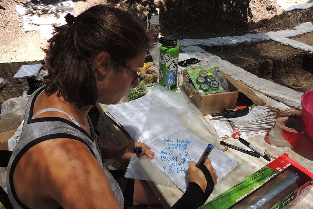 Student Ariel Polokoff on a dig site making notes on paper about artifacts around her